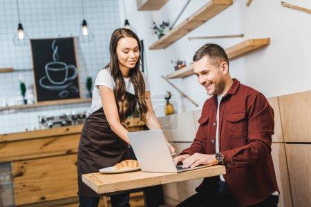 Foto de Atractiva camarera junto a freelancer sentado en la mesa, mirando a la laptop y sonriendo en café - Imagen libre de derechos