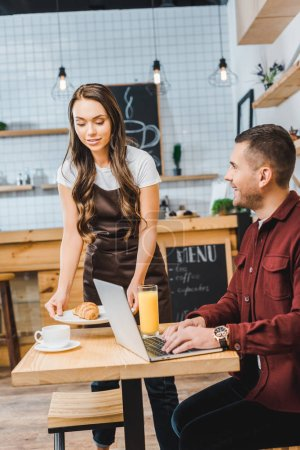 Photo for Attractive waitress holding plate with croissant near freelancer sitting at table with laptop and smiling in coffee house - Royalty Free Image