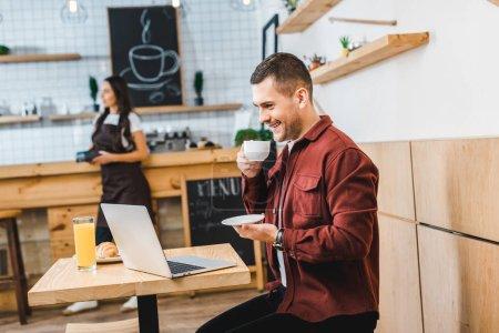 Foto de Enfoque selectivo de independiente guapo sentado en mesa con ordenador portátil y beber camarera de wile café permanente cerca de barra de bar en café - Imagen libre de derechos