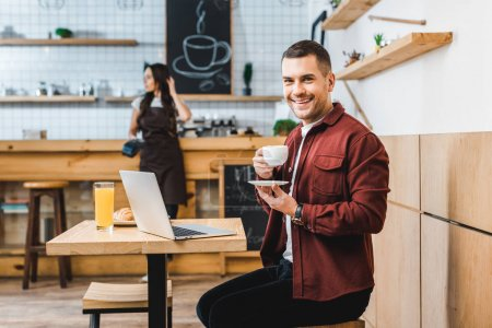 Photo for Handsome freelancer sitting at table with laptop, drinking coffee and smiling wile waitress standing near bar in coffee house - Royalty Free Image