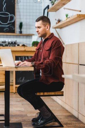 Schöne Freiberuflerin im weinroten Hemd sitzt mit Laptop am Tisch und tippt im Kaffeehaus