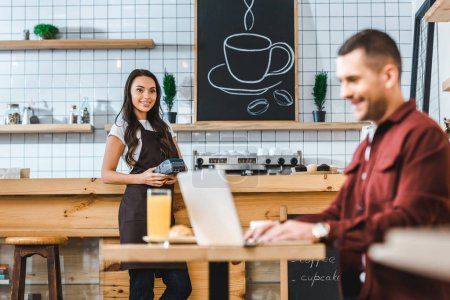 Photo for Selective focus of waitress standing near bar counter with terminal wile freelancer in burgundy shirt sitting at table in coffee house - Royalty Free Image
