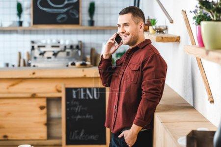 schöner Mann in weinrotem Hemd und Jeans steht, lächelt und spricht auf Smartphone im Kaffeehaus