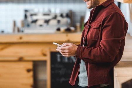 vista recortada del hombre en camisa de color burdeos de pie con teléfono inteligente en la cafetería