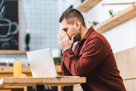 Foto de Guapo freelance preocupado en Borgoña camisa sentados en mesa con ordenador portátil y vaso de jugo de café - Imagen libre de derechos