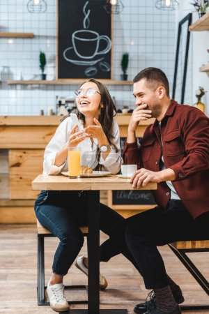 Photo for Attractive brunette woman and handsome man in burgundy shirt sitting at table, laughing and looking to smartphone in coffee house - Royalty Free Image