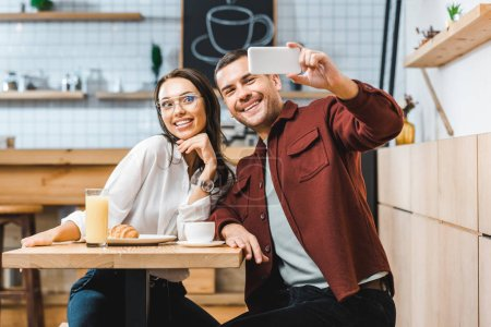 Photo for Attractive brunette woman and handsome man in burgundy shirt sitting at table and taking selfie to smartphone in coffee house - Royalty Free Image