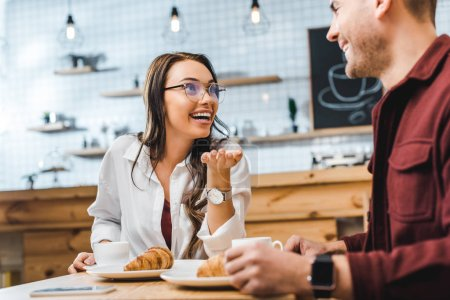 Photo for Attractive brunette woman and handsome man in burgundy shirt sitting at table with croissants, smiling and talking in coffee house - Royalty Free Image