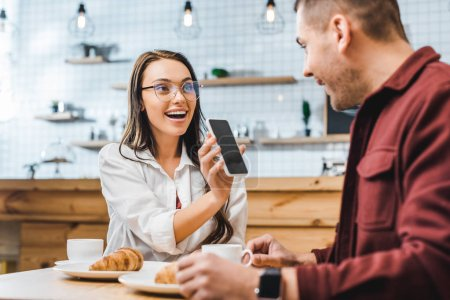 attractive brunette woman sitting at table and showing smartphone with blank screen to handsome man in burgundy shirt in coffee house