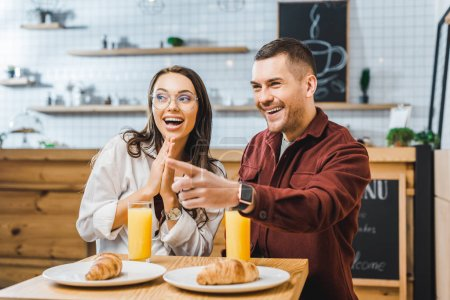 Photo for Attractive brunette woman and handsome man in burgundy shirt sitting and smiling at table with croissants and glasses of juice in coffee house - Royalty Free Image