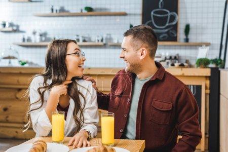 attraktive brünette Frau und schöner Mann in weinrotem Hemd sitzen am Tisch, lachen und schauen einander im Kaffeehaus an