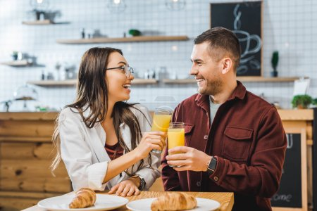 Photo for Attractive brunette woman and handsome man in burgundy shirt sitting at table with croissants, smiling and clinking glasses with juice in coffee house - Royalty Free Image