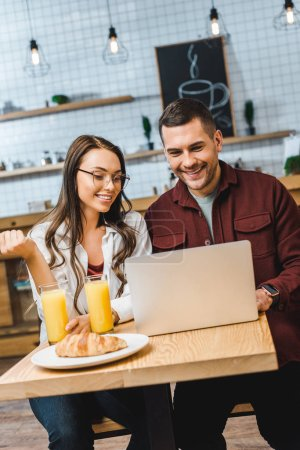 beautiful brunette woman and handsome man sitting at table, smiling and looking to laptop in coffee house