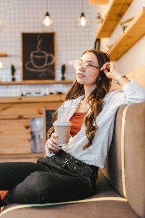 mujer atractiva en camisa blanca y vaqueros negros sentados en el sofá y sosteniendo la taza de papel en la cafetería