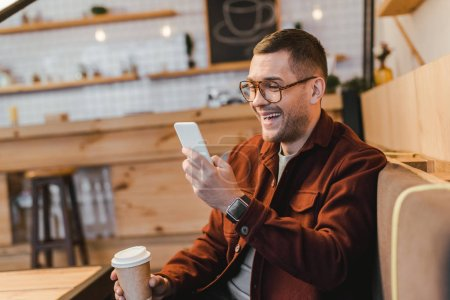 handsome man in burgundy shirt sitting on couch, holding paper cup, looking to smartphone and laughing in coffee house
