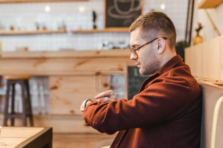 handsome man in burgundy shirt sitting on couch and touching watch with finger  in coffee house