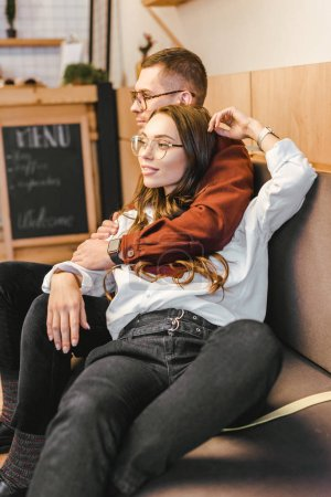 attractive woman and man in glasses sitting on couch and hugging in coffee house