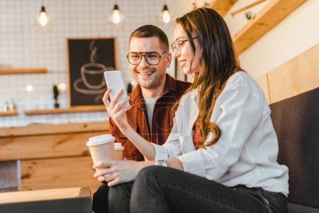 Photo pour Séduisante femme et bel homme assis sur le canapé, tenant des tasses en papier et regardant smartphone dans le café - image libre de droit