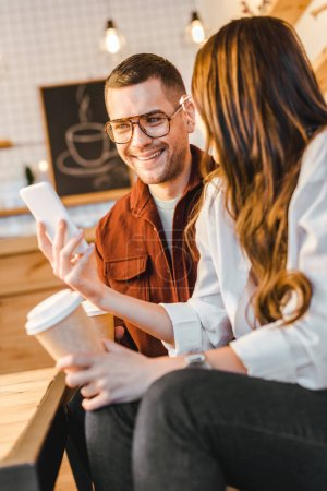 brunette woman and handsome man sitting on couch, holding paper cups and looking to smartphone in coffee house