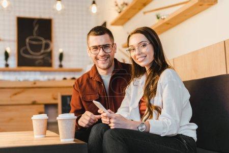 Photo pour Séduisante femme souriante, tenant smartphone et assise sur le canapé avec un bel homme à table avec des tasses en papier dans un café - image libre de droit