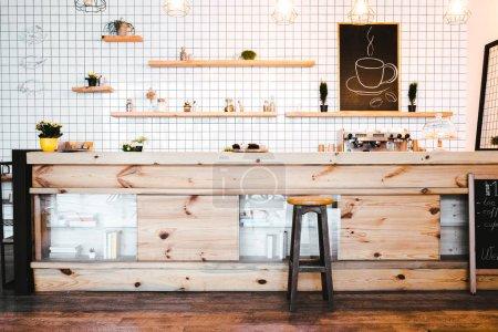 Photo pour Comptoir de bar brun en bois avec des plantes et des cupcakes, dessin sur étagère dans le café - image libre de droit