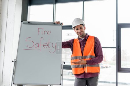 Photo for Cheerful firefighter in helmet gesturing while standing near white board with fire safety lettering - Royalty Free Image