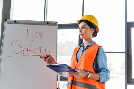 Photo for Female firefighter in helmet holding clipboard and pen while standing near white board with fire safety lettering - Royalty Free Image