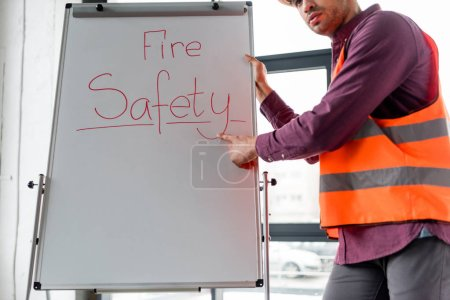 Photo for Cropped view of fireman pointing with finger while standing near white board with fire safety lettering - Royalty Free Image