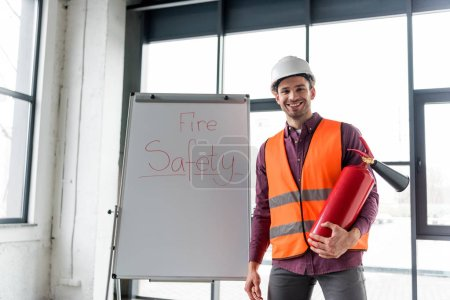 happy fireman holding red extinguisher while standing near white board with fire safety lettering