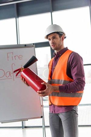 Photo pour Beau pompier tenant un extincteur rouge et debout près du tableau blanc avec lettrage de sécurité incendie - image libre de droit