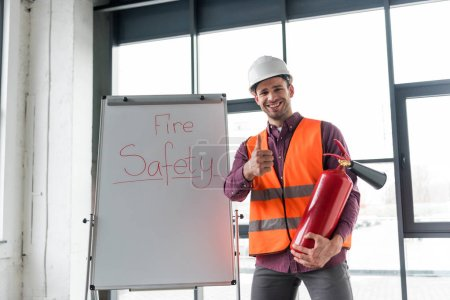 Photo for Cheerful fireman holding red extinguisher and showing thumb up while standing near white board with fire safety lettering - Royalty Free Image