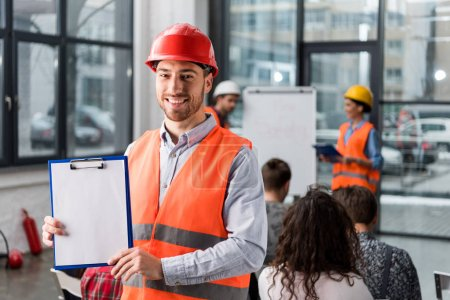 cheerful fireman holding blank clipboard near coworkers giving talk on briefing