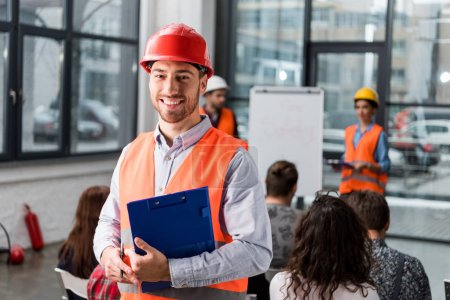cheerful fireman holding clipboard near coworkers giving talk on briefing