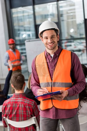 selective focus of cheerful fireman holding clipboard near coworker giving talk on briefing