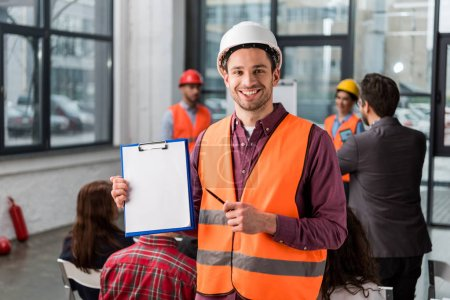 Photo for Selective focus of cheerful fireman pointing at blank clipboard with pen near coworkers giving talk on briefing on background - Royalty Free Image