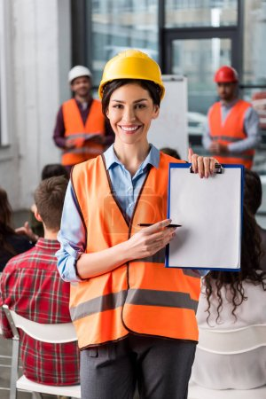 Photo for Selective focus of cheerful female firefighter pointing at blank clipboard with pen near coworkers giving talk on briefing on background - Royalty Free Image