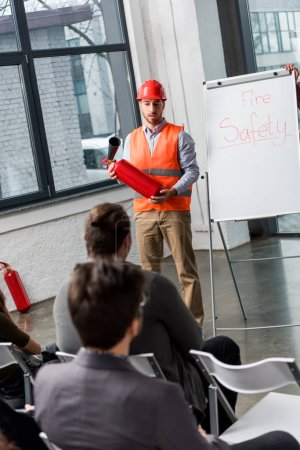 Photo for Handsome fireman in helmet giving talk on briefing while holding extinguisher near white board with fire safety lettering - Royalty Free Image