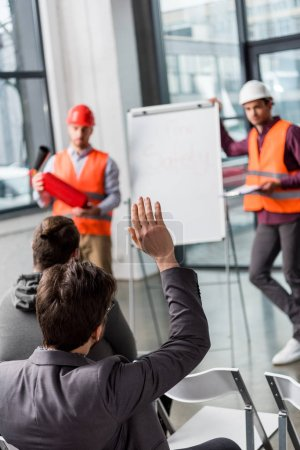 Photo for Selective focus of man raising hand near handsome firemen in helmets standing near white board with fire safety lettering - Royalty Free Image