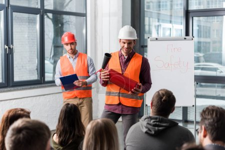 Photo for Selective focus of handsome firemen in helmets standing near white board with fire safety lettering and holding extinguisher and clipboard in hands - Royalty Free Image