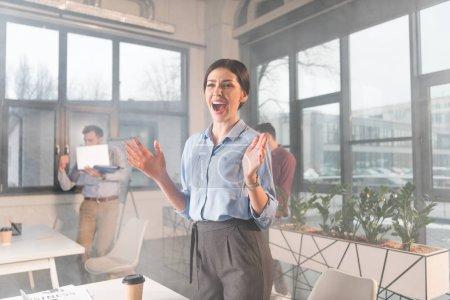 Photo pour Femme d'affaires attrayant debout et hurlant près de vos collègues au bureau avec de la fumée - image libre de droit