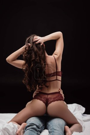 Photo for Back view of woman in sexy lingerie sitting on top of man in bed isolated on black - Royalty Free Image