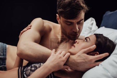 Photo pour Bel homme embrassant doucement belle femme au lit isolé sur noir - image libre de droit
