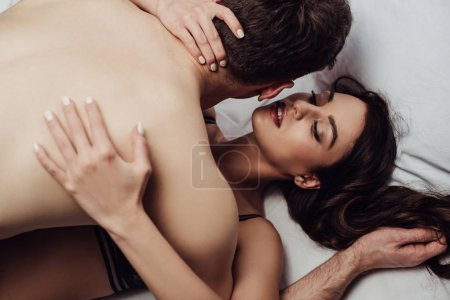 Photo for Selective focus of young sexy couple passionately embracing in bed - Royalty Free Image