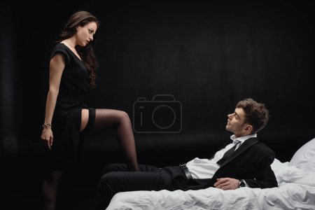 Photo for Handsome man lying on bed and looking at beautiful sexy woman in stockings isolated on black - Royalty Free Image