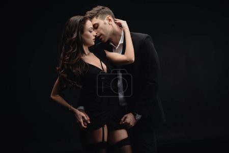Photo for Beautiful woman passionately embracing handsome man in formal wear isolated on black - Royalty Free Image