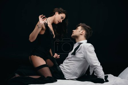 Photo for Beautiful young woman in sexy lingerie undressing man isolated on black - Royalty Free Image