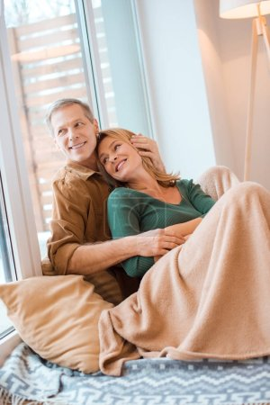 Photo for Smiling couple hugging while sitting on floor by large window at new home - Royalty Free Image