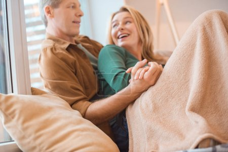 Photo for Selective focus of happy couple holding hands while resting under soft fleece blanket - Royalty Free Image