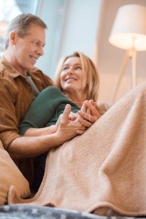 Photo pour Foyer sélectif de couple heureux reposant sous la couverture polaire douce - image libre de droit