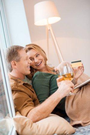 Photo pour Gentil couple regardent tout en utilisant l'ordinateur portable ensemble - image libre de droit
